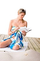 Beach _ woman sitting on wooden deck with book, sunbathing, wearing pareo
