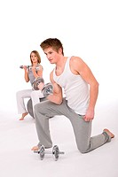 Fitness _ Young healthy couple exercise with metal weights on white background