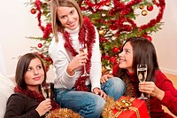 Three young women having fun on Christmas in front of tree
