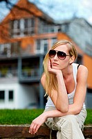 Young woman with sunglasses waiting in front of a house