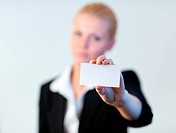 Business woman holding out a business card with the camera focus pin sharp on the card