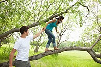 Young man helps a young woman walk across a tree branch.