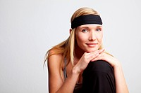 Young releaxed woman with black headband smiling