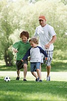 Father plays soccer with his two young sons.