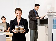Businesswoman carrying tray of coffee