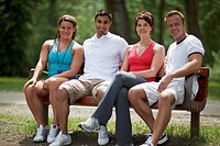 Group of friends in active and casual wear smile while seated on a park bench.