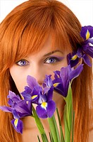 beauty portrait of young redhead woman hidding face behind flowers