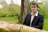 Junger Manager lehnt sich im Park auf einen umgestützten Baumstamm
