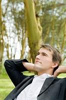 Junger Manager ruht sich mit Händen hinter dem Kopf auf einer Waldlichtung aus