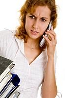 Junge Frau mit Akten unter dem Arm ärgert sich bei ihrem Handy_Telefonat Model: Daniela L.