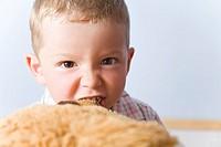 Vierjähriger Junge beisst grimmig in seinen Teddybär