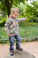 Vierjähriger Junge steht im Park auf einem Felsen