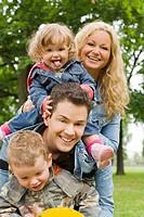 Lachende Familie mit Tochter und Sohn zusammen auf einem Schaukeltier auf einem Spielplatz