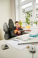 Mann im Anzug legt seine Füße auf den Schreibtisch und spielt Akustikgitarre