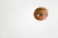 Mann schaut mit seinem Auge durch ein Guckloch