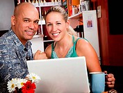 Attractive couple in a coffee house with laptop computer