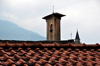 View over old roofs of Italian city showing ancient church and bell tower