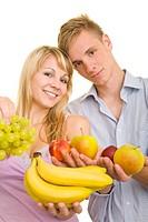 Junge blonde Frau mit langen Haaren und junger Mann halten lachend buntes Obst in den Händen