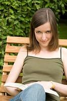 Junge Frau liest im Garten auf einer Holzliege ein Buch Model: Wencke Landsmann