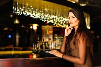 Smiling woman standing at bar