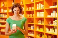 Kundin in Apotheke liest Informationen auf Medikament
