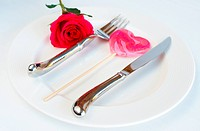 Valentines day table setting with a white plate, single pink rose and heart shaped lolly