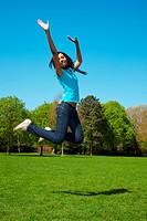 Junge Afrikanerin im Park springt hoch in die Luft