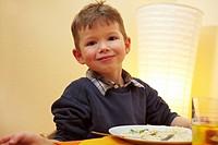 Grinsender blonder Junge sitzt vor Teller am Tisch