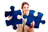 Zufriedene Geschäftsfrau hält zwei große Puzzleteile