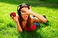 Woman with headphones listening music on the grass