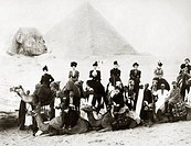 A group of European tourists on a guided camel tour pose to have their photograph taken at Giza, c1890s.