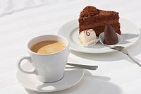 a cup of coffee and a piece of chocolate cake on white background