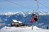 Skifahrer im Sessellift über der Schutzhütte Les Violettes des Schweizer Alpenclubs in den Walliser Bergen, Crans Montana, Wallis, Schweiz / Skiers si...