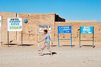 Junge spielt Fußball in einem Dorf in der Wüste, dahinter Hinweisschilder zu Hotel Kasbahs, Hassi Labid, Südmarokko, Afrika