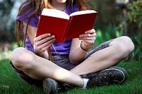 Ein Kind sitzt im Garten auf einer Wiese und liest ein Buch