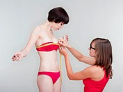 two young female friends measuring results of diet - isolated on gray