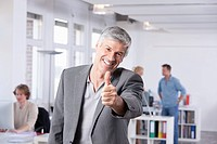 Germany, Bavaria, Munich, Mature man showing thumbs up, colleagues in background