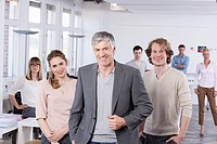 Germany, Bavaria, Munich, Mature man with colleagues standing in office, smiling