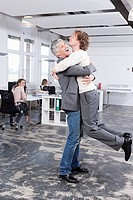 Germany, Bavaria, Munich, Men embracing in office, colleagues working in backgrounds
