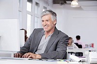 Germany, Bavaria, Munich, Mature man using computer, colleagues working in background
