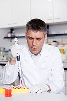 Germany, Bavaria, Munich, Scientist pouring red liquid with pipette in test tube for medical research in laboratory