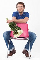 Mid adult man sitting on chair with roses, smiling