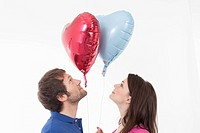 Couple looking at heart shaped balloons
