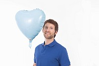 Mid adult man with heart shaped balloon, smiling, portrait