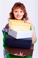expression portrait of happy young shopaholic woman walking with shoes boxes