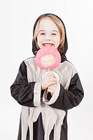 Boy in fancy dress costume with candy, portrait