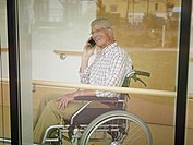 Germany, Cologne, Senior man on phone in nursing home, smiling