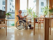 Germany, Cologne, Senior woman reading newspaper in nursing home