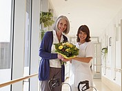 Germany, Cologne, Senior women and caretaker holding bouquet in corridor of nursing room, smiling, portrait