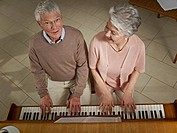 Germany, Cologne, Senior couple playing piano in nursing home